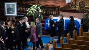 People line up to pay their respect to former Quebec premier Bernard Landry, who died last week, and extend their condolences to his wife Chantal Renaud, centre, during a public viewing in Montreal on Monday, Nov. 12, 2018. (Paul Chiasson / THE CANADIAN PRESS)