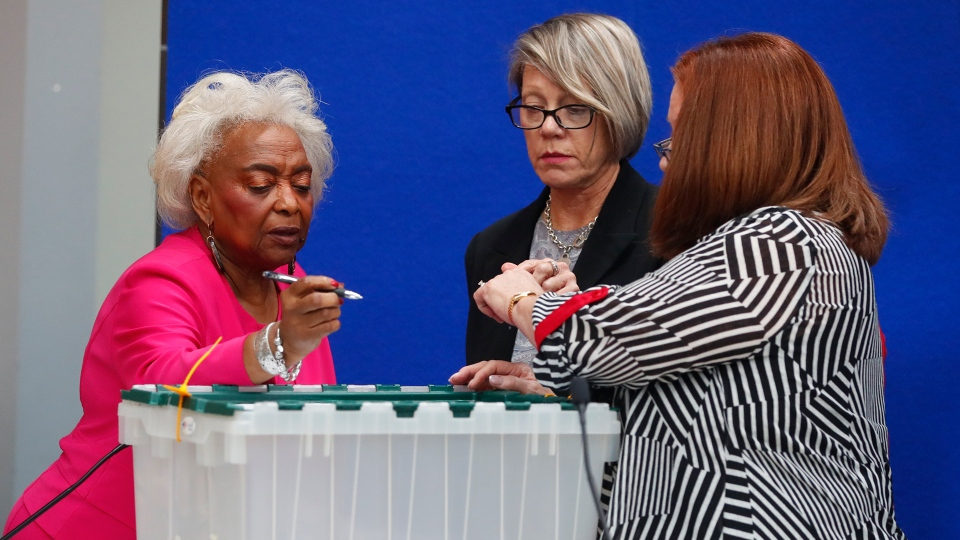 Broward County Supervisor of Elections Brenda Snipes, left, Board chair Judge Betsy Benson, centre, and Board member Judge Deborah Carpenter-Toye, sign off on a sealed bin that will be sent to the capitol as ballots have begun to be sorted before counting, Monday, Nov. 12, 2018, in Lauderhill, Fla. (AP / Wilfredo Lee)