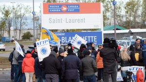 Striking Canada Post workers walk the picket line in front of the Saint-Laurent sorting facility in Montreal on Tuesday October 30, 2018. THE CANADIAN PRESS/Ryan Remiorz