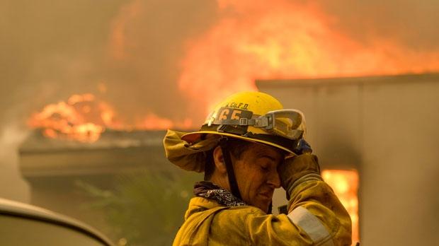 A firefighter keeps watch as the wildfire burns a home near Malibu Lake in Malibu, Calif., Friday, Nov. 9, 2018. (AP Photo/Ringo H.W. Chiu, File)