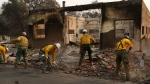 Fire crews clear rubble from the road near a building burned in the Camp Fire, Monday, Nov. 12, 2018, in Paradise, Calif. (AP / John Locher)