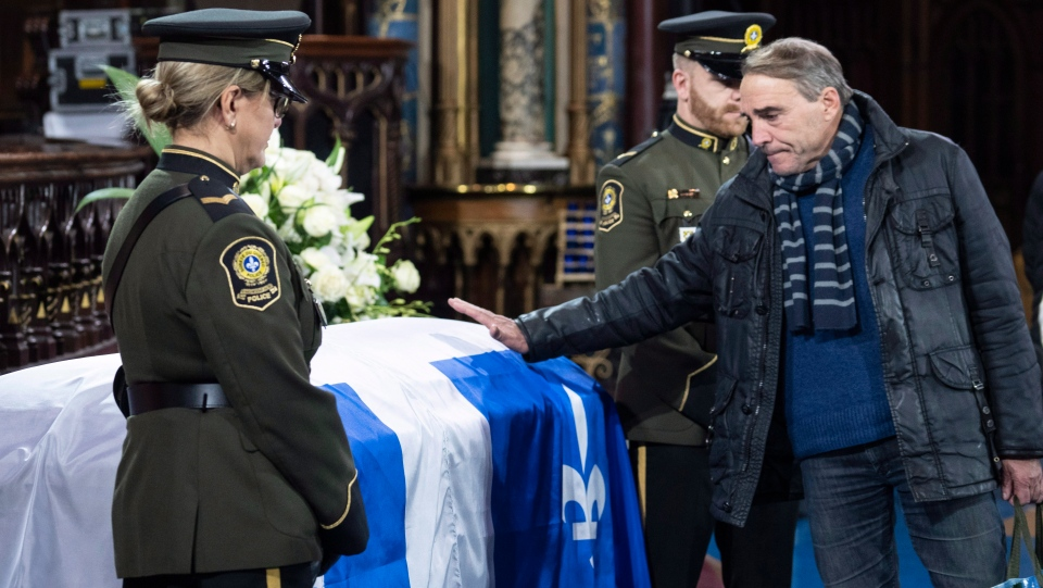 Actor Pierre Chagnon touches the casket of former Quebec premier Bernard Landry, who died last week, during a public viewing in Montreal on Monday, November 12, 2018. (THE CANADIAN PRESS/Paul Chiasson)