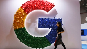 In this Monday, Nov. 5, 2018, photo, a woman carries a fire extinguisher past the logo for Google at the China International Import Expo in Shanghai. (AP Photo/Ng Han Guan)