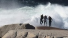 This photo, taken Nov. 11, 2018, shows some tourists getting drenched by a wave while walking too far out on the rocks at Peggy's Cove. (Jane MacDonald-O'Connell/Facebook)