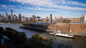 In this Wednesday, Nov. 7, 2018, photo, a rusting ferryboat is docked next to an aging industrial warehouse on Long Island City's Anable Basin in the Queens borough of New York. (AP Photo/Mark Lennihan)