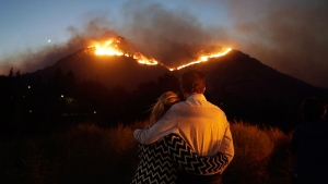 Roger Bloxberg, right, and his wife Anne hug as they watch a wildfire on a hill top near their home Friday, Nov. 9, 2018, in West Hills, Calif. (AP Photo/Marcio Jose Sanchez)