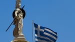 A Greek flag waves by the statue of the goddess Athina, in Athens, Friday, June 22, 2012.(AP Photo/Petros Karadjias)