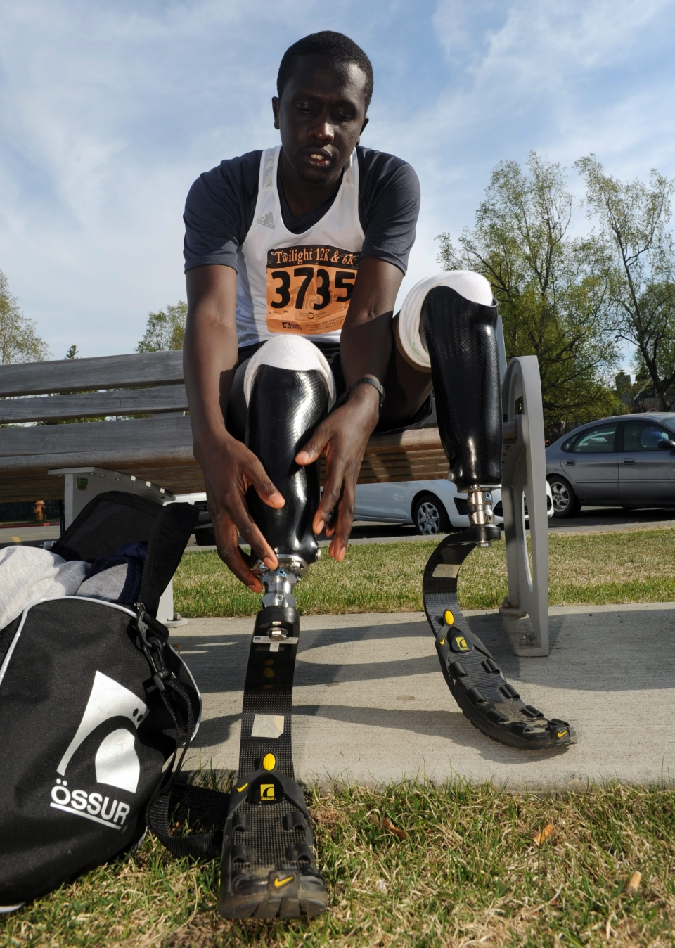In this May 31, 2013 photo, Marko Cheseto prepares to race the Skinny Mini 6K, attaching his new carbon-fiber running blades to his prosthetic legs after removing prosthetic feet and shoes in downtown Anchorage, Alaska. (AP Photo/The Anchorage Daily News, Erik Hill)