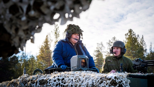 Norway's Prime Minister Erna Solberg, left, drives in a Leopard 2 battle tank in the Roros area, mid Norway, during her visit to NATO exercises Saturday Oct. 27, 2018. (Heiko Junge, NTB scanpix via AP)