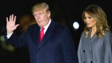 U.S. President Donald Trump waves as he walks with first lady Melania Trump, after stepping off Marine One, on the South Lawn of the White House, Sunday, Nov. 11, 2018, in Washington. (AP Photo/Alex Brandon)