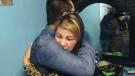 Zakiyeh Rezaee gives her son, Reza Hassani, a hug.