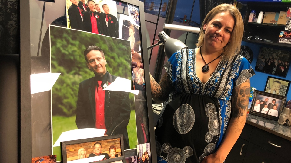Cheryl Wenzel stands with her late husband's photos at Electric Underground Tattoos. (Angelina King/CTV Saskatoon)