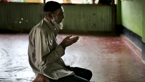 In this photograph taken Aug. 24, 2018, Rohingya faith healer Abul Kalam, 60, prays at a makeshift mosque in Kutupalong refugee camp, Bangladesh. (AP Photo/Altaf Qadri)