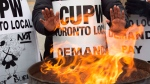 Striking Canada Post workers keep their hands warm as they picket at the South Central sorting facility in Toronto on Tuesday, November 13, 2018. (Frank Gunn / THE CANADIAN PRESS)