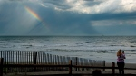 In this Tuesday, June 5, 2018 photo, Kristal Painter, of French Lick, Ind., pauses on the beach to photograph a rainbow over the ocean after a rain storm passed through Atlantic City, N.J. Painter is in town attending a travel industry convention. (Tim Gralish/The Philadelphia Inquirer via AP)