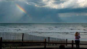 In this Tuesday, June 5, 2018 photo, Kristal Painter, of French Lick, Ind., pauses on the beach to photograph a rainbow over the ocean after a rain storm passed through Atlantic City, N.J. (Tim Gralish/The Philadelphia Inquirer via AP)
