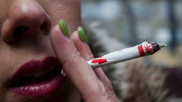 "A woman smokes a marijuana joint at a ""Wake and Bake"" legalized marijuana event in Toronto on Wednesday, October 17, 2018. THE CANADIAN PRESS/Christopher Katsarov"