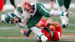 University of Saskatchewan Huskies' Tyler Chow is stopped by University of Calgary Dinos' Matthew Lucyshyn during Hardy Cup CWUAA championship football action in Calgary, Saturday, Nov. 10, 2018. THE CANADIAN PRESS/Todd Koro