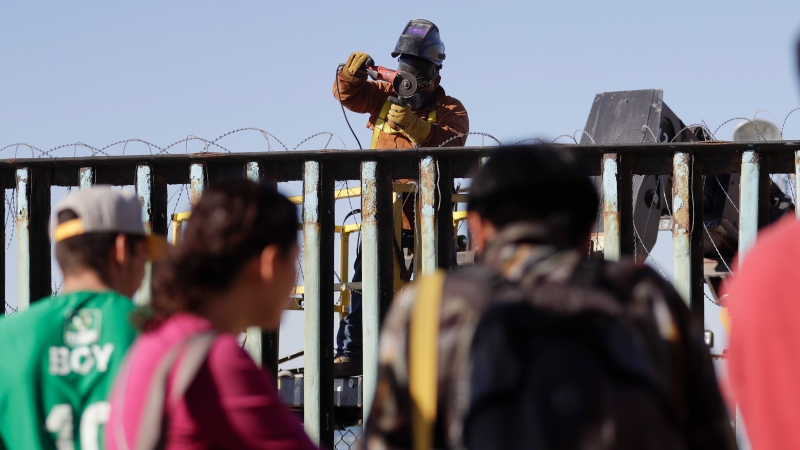 A man installs concertina wire on top of the border structure on the U.S. side as Central American migrants and others look on Wednesday, Nov. 14, 2018, in Tijuana, Mexico. (AP / Gregory Bull)