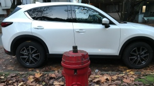 A SUV is seen parked in front of a fire hydrant.