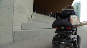 Elaine Lee looks at the stairs from her wheelchair outside the new central library in East Village