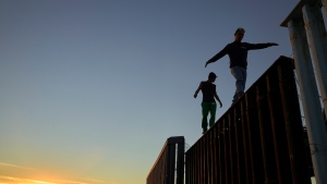 Two Central American migrants walk along the top of the border structure separating Mexico and the United States Wednesday, Nov. 14, 2018, in Tijuana, Mexico.  (AP Photo/Gregory Bull)