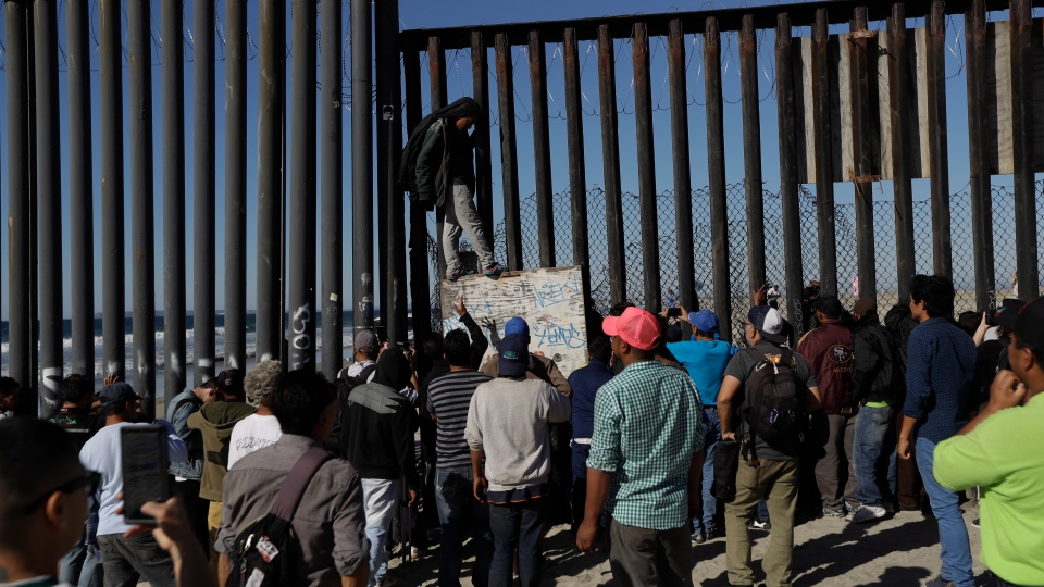Central American migrants and others look on along the border structure, in Tijuana, Mexico, Wednesday, Nov. 14, 2018. (AP / Gregory Bull)
