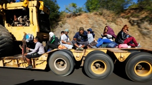 Migrants traveling with a caravan hoping to reach the U.S. border, ride on the bed of a truck, on the highway between Mazatlan and Cualiacan, Mexico, Wednesday, Nov. 14, 2018. The bulk of the main caravan appeared to be about 1,100 miles from the border, but was moving hundreds of miles per day. (AP Photo/Marco Ugarte)