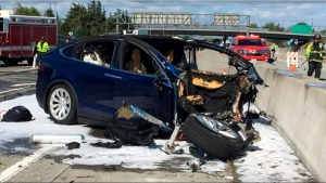In this March 23, 2018 file photo provided by KTVU, emergency personnel work a the scene where a Tesla electric SUV crashed into a barrier on U.S. Highway 101 in Mountain View, Calif. (KTVU via AP, File)