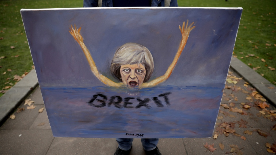 Political artist Kaya Mar holds a painting depicting British Prime Minister Theresa May sinking in 'a sea of Brexit' in London, on Nov. 15, 2018. (Matt Dunham / AP)