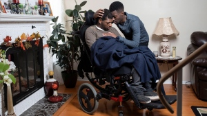 Stephane Alexis embraces his brother Torence, left, as they are photographed in their family home in Ottawa on Wednesday, Nov. 14, 2018. Stephane helps provide care for his brother, who has cerebral palsy. (THE CANADIAN PRESS / Justin Tang)