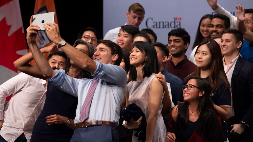 Canadian Prime Minister Justin Trudeau takes a selfie with youth following an armchair discussion at the National University of Singapore in Singapore, Thursday, November 15, 2018. THE CANADIAN PRESS/Adrian Wyld