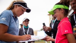 Brooke Henderson, of Canada, signs a flag for Gracie Grant, 12, of Destin, during the CME Group Tour Championship golf tournament, Thursday, Nov. 15, 2018, at Tiburon Golf Club in Naples, Fla. (Alex Driehaus/Naples Daily News via AP)
