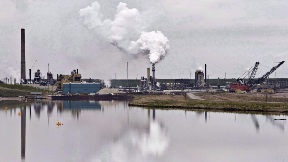 The Syncrude oil sands extraction facility is reflected in a tailings pond near the city of Fort McMurray, Alta. on Sunday, June 1, 2014. THE CANADIAN PRESS/Jason Franson