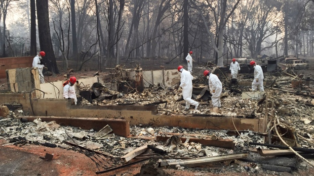 Volunteer rescue workers search for human remains in the rubble of homes burned in the Camp Fire in Paradise, Calif., Thursday, Nov. 15, 2018. Dozens of people died and perhaps several hundred are unaccounted for in the nation's deadliest wildfire in a century. (AP Photo/Terry Chea)