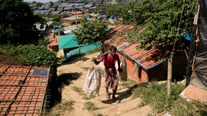A Rohingya refugee carries plastic sacks filled with food at Jamtoli refugee camp, near Cox's Bazar, in Bangladesh, Thursday, Nov. 15, 2018. The head of Bangladesh's refugee commission said plans to begin a voluntary repatriation of Rohingya Muslim refugees to their native Myanmar on Thursday were scrapped after officials were unable to find anyone who wanted to return. (AP Photo/Dar Yasin)