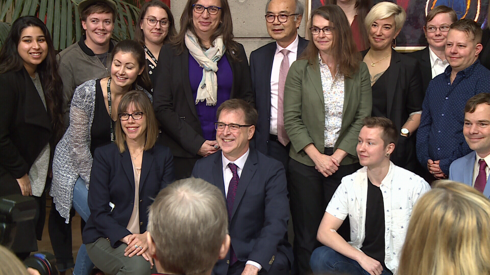 Health Minister Adrian Dix, centre, poses at a B.C. government announcement on gender-affirming surgeries. Nov. 16, 2018.