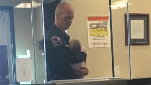Patrol officer Robert Lofgran held a young mother's baby for hours as the mother filed a domestic violence report. (West Jordan Police Department)