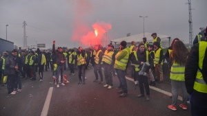 """Demonstrators block the Prado's roundabout, southern France, Saturday, Nov. 17, 2018, to protest fuel taxes in Marseilles; their yellow jackets read: """"Tax planes"""" """"Tax boats"""" (AP Photo/Claude Paris)"""