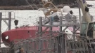 Coast Guard ship partially submerged, on its side after sliding down slip
