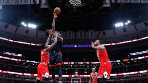 Toronto Raptors forward Serge Ibaka (9) shoots as Chicago Bulls forwards Justin Holiday (7) and Jabari Parker (2) defend during the second half of an NBA basketball game Saturday, Nov. 17, 2018, in Chicago. (AP Photo/Kamil Krzaczynski)