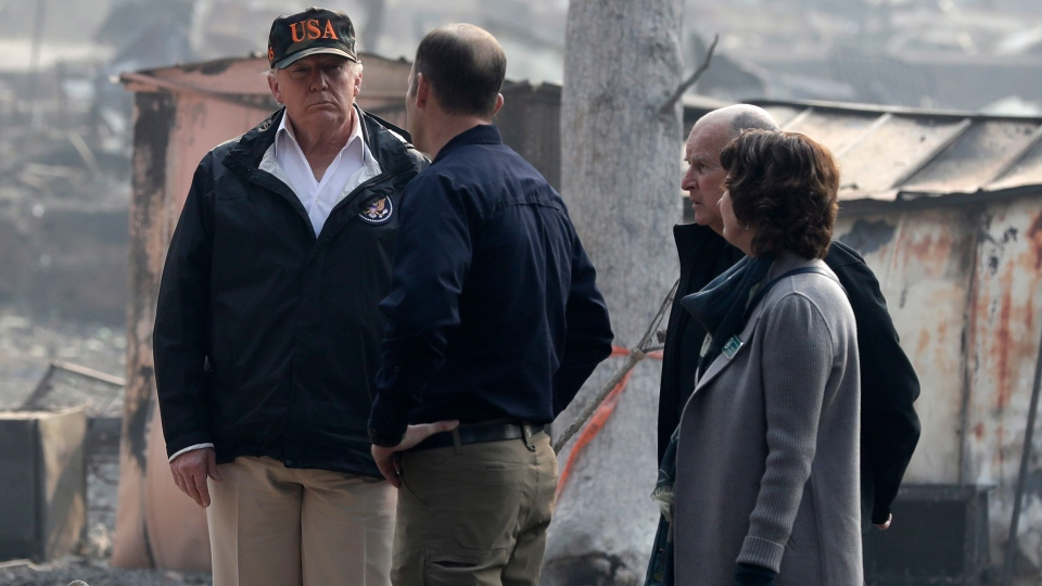 U.S. President Donald Trump talks with FEMA Administrator Brock Long, Jody Jones, Mayor of Paradise, and California Gov. Jerry Brown, second from right during a visit to a neighborhood impacted by the wildfires, Saturday, Nov. 17, 2018, in Paradise, Calif. (AP Photo/Evan Vucci)