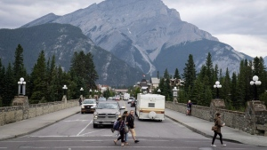 Pedestrians cross the street in Banff, Alta., in Banff National Park on July 21, 2017. THE CANADIAN PRESS/Jeff McIntosh