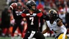 Ottawa Redblacks' Trevor Harris (7) throws the ball as Hamilton Tiger-Cats' Don Unamba (1) defends, during first half CFL East Division final football action in Ottawa on Sunday, Nov. 18, 2018. (Justin Tang/The Canadian Press via AP)