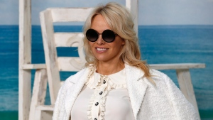 Pamela Anderson poses during a photocall before the presentation of Chanel Spring/Summer 2019 ready-to-wear fashion collection in Paris, Tuesday, Oct.2, 2018. (AP Photo/Christophe Ena)