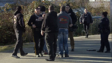 Men wearing Hells Angels insignia speak with RCMP officers after crossing underneath police tape at a Maple Ridge, B.C. crime scene. Nov. 18, 2018.