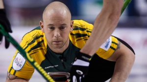 Northern Ontario third Ryan Fry makes a shot as his team plays Newfoundland and Labrador during curling action at the Brier in Calgary, Thursday, March 5, 2015. A curling team skipped by Jamie Koe of the Northwest Territories which included Olympic gold medal winner Ryan Fry has been ejected from a big Alberta bonspiel for what organizers call unsportsmanlike behaviour resulting from public drunkenness. (THE CANADIAN PRESS / Jeff McIntosh)