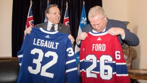 Quebec Premier Francois Legault, left, exchanges hockey jerseys with Ontario Premier Doug Ford at Queens Park, in Toronto on Monday, Nov. 19, 2018. (THE CANADIAN PRESS/Chris Young)