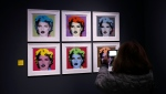 "A woman takes pictures during a press preview of the ""A Visual Protest. The Art of Banksy"" exhibition dedicated to British artist Banksy, in Milan, Italy, Tuesday, Nov. 20, 2018. (AP Photo/Antonio Calanni)"