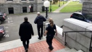 Two key officials at British Columbia's legislature were placed on indefinite leave today and were escorted out of the building by security officials. B.C. legislature Sergeant-at-Arms Gary Lenz, centre, is escorted out of the legislature by security, in Victoria on Tuesday, Nov. 20, 2018. (THE CANADIAN PRESS/Dirk Meissner)